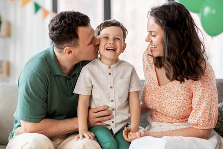 happy parents kissing little son at birthday party Фото со стока
