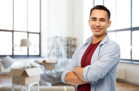smiling young man over new home background