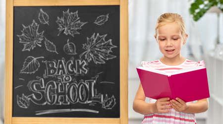smiling little student girl reading book