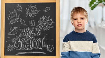 bored little student boy over school blackboard