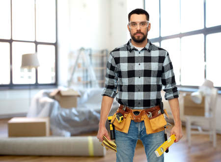 male builder with tools and level at home