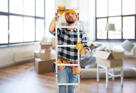 male builder in helmet climbing up ladder at home
