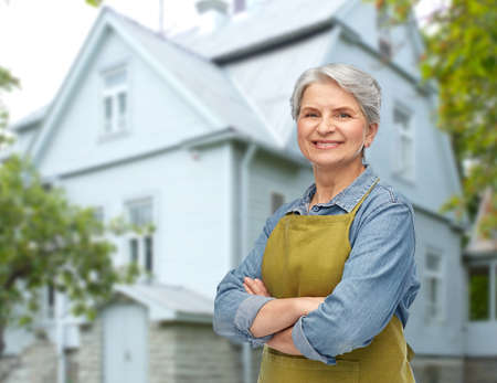 portrait of smiling senior woman in garden apron