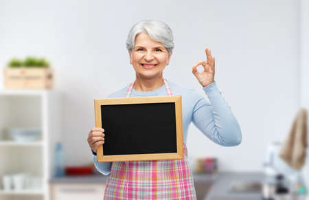 senior woman in apron with chalkboard showing ok