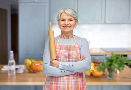 smiling senior woman in apron with rolling pin Foto de archivo
