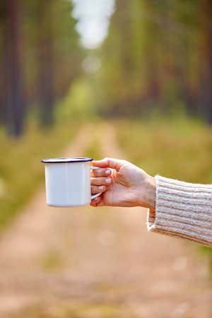 hand of woman with white tea mug in forest