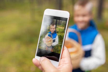 parent photographing grandson with mushrooms Foto de archivo