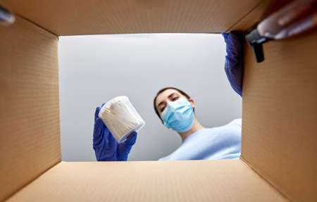 woman in mask unpacking parcel box with cosmetics