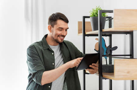 happy smiling man with tablet pc at shelf at home