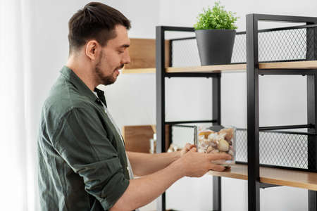 man decorating home with seashells in vase