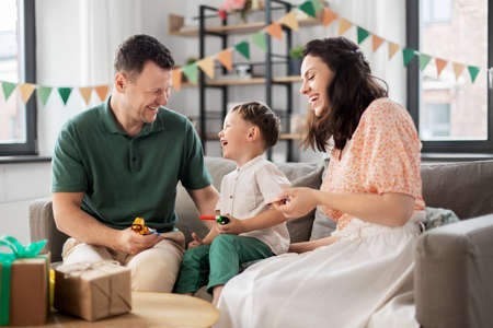 happy family with gifts and party blowers at home