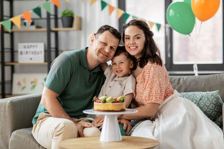 happy family with birthday cake hugging at home
