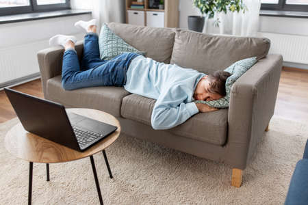 bored man with laptop lying on sofa at home