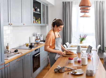 woman cooking food and baking on kitchen at home
