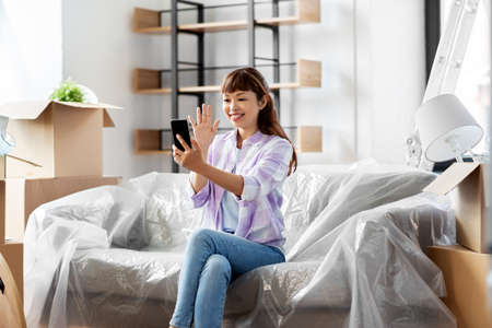 woman with phone having video call at new home