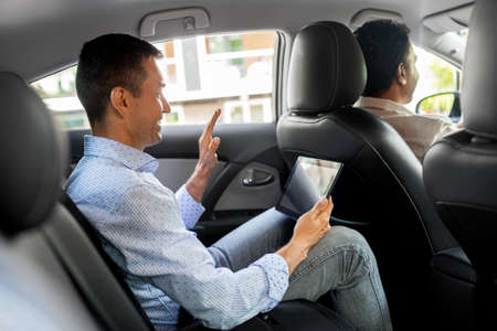 man with tablet pc having video call in taxi car
