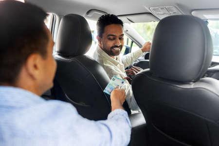 passenger giving money to smiling taxi car driver Foto de archivo