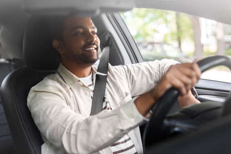 smiling indian man or driver driving car Foto de archivo