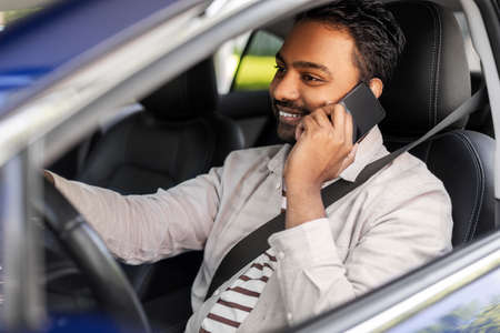 indian man driving car and calling on smartphone