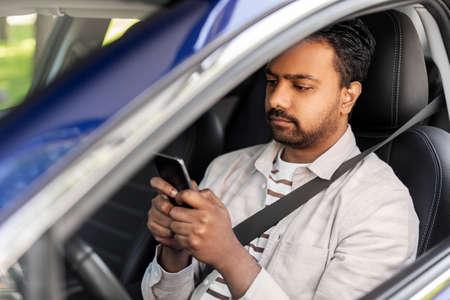 indian man in car using smartphone