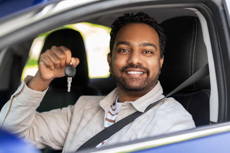 smiling indian man or driver showing car key
