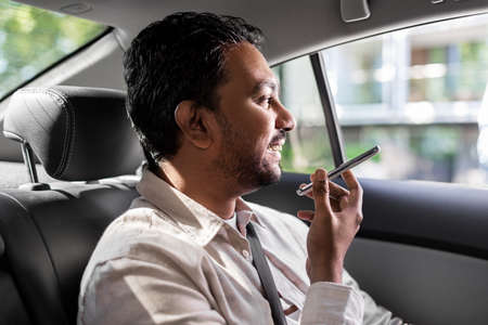 male passenger calling on smartphone in taxi car