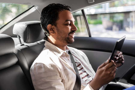 indian male passenger with tablet pc in taxi car