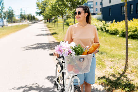 woman with food and flowers in bicycle basket