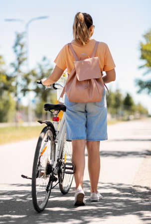 woman with bicycle and backpack walking in city