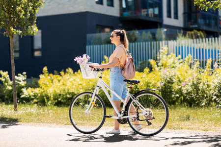 woman with flowers in bicycle basket in city