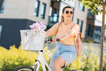 happy woman with earphones riding bicycle in city