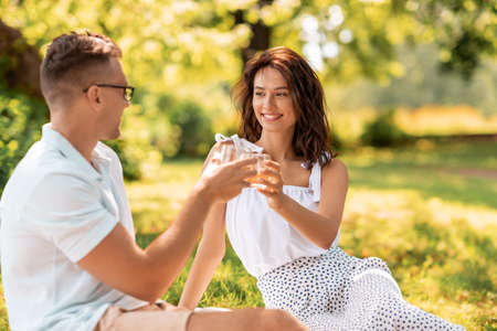 happy couple toasting drinks at summer park