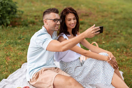 happy couple taking selfie at picnic in park
