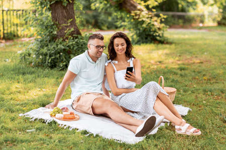 happy couple with smartphone at picnic in park