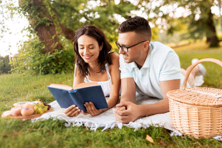 happy couple reading book on picnic at summer park