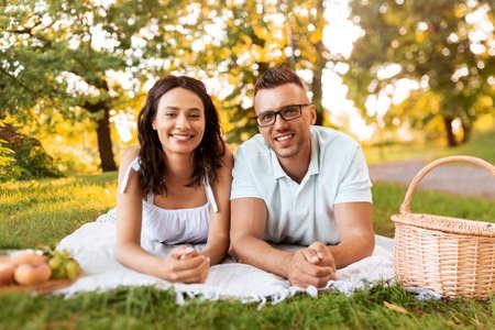 happy couple on picnic blanket at summer park Foto de archivo