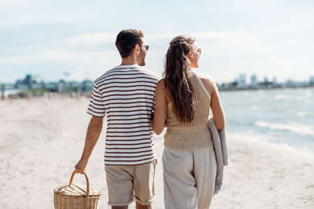 happy couple with picnic basket walking on beach