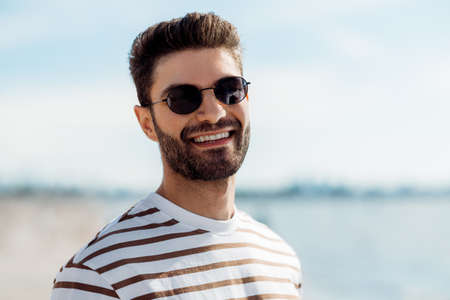 smiling young man in sunglasses on summer beach Foto de archivo