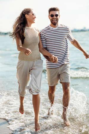 happy couple running along summer beach Foto de archivo