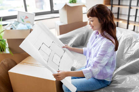 woman with blueprint and boxes moving to new home Zdjęcie Seryjne