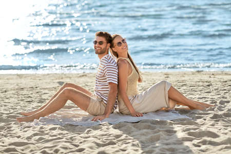 happy couple sitting back to back on summer beach