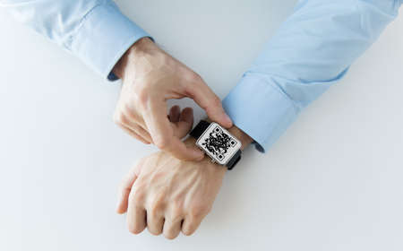 mans hands with qr code on smart watch