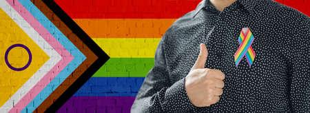 close up of man with gay pride ribbon shows thumb Zdjęcie Seryjne