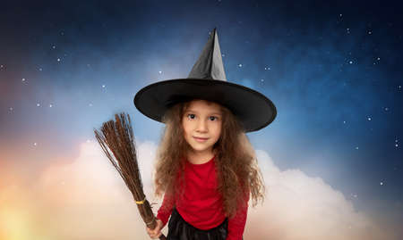 girl in witch hat with broom on halloween at night Zdjęcie Seryjne