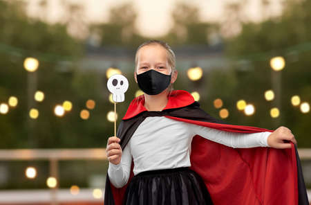 girl in mask and costume of dracula on halloween