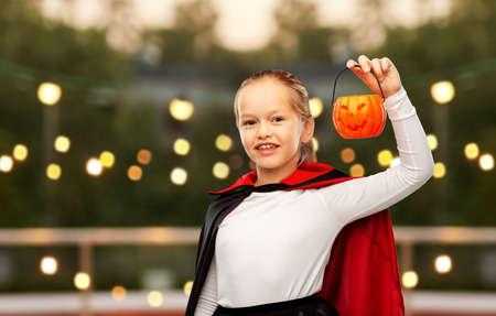 girl in halloween costume of dracula with pumpkin