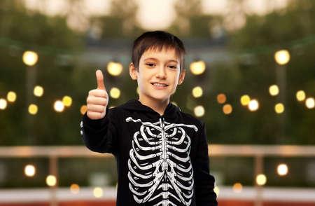 boy in halloween skeleton costume shows thumbs up Zdjęcie Seryjne
