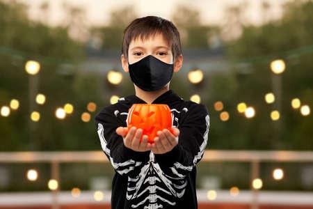 boy in mask and halloween costume with pumpkin Zdjęcie Seryjne
