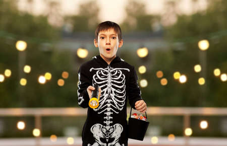 boy in halloween costume with candies and torch