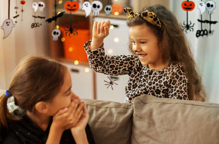 girls in halloween costumes playing with spider Zdjęcie Seryjne